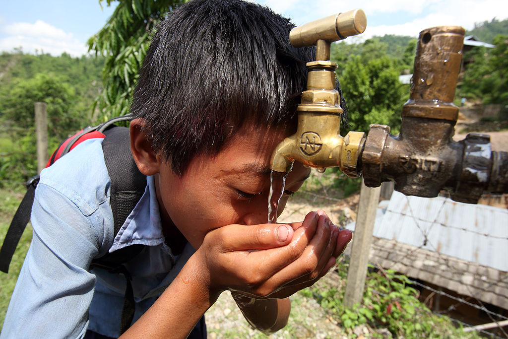 Boy_drinks_from_a_tap_at_a_NEWAH_WASH_water_project_in_Puware_Shikhar,_Udayapur_District,_Nepal._(10677903803)